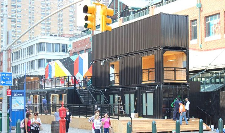 People walking on the street and enjoying restaurants made completely out of shipping containers